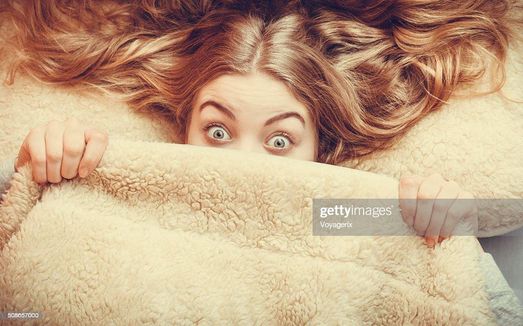 Woman waking up under wool woolen blanket. : Stock Photo