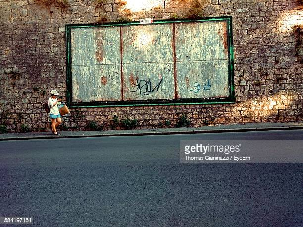 Woman Waling On Street By Wall
