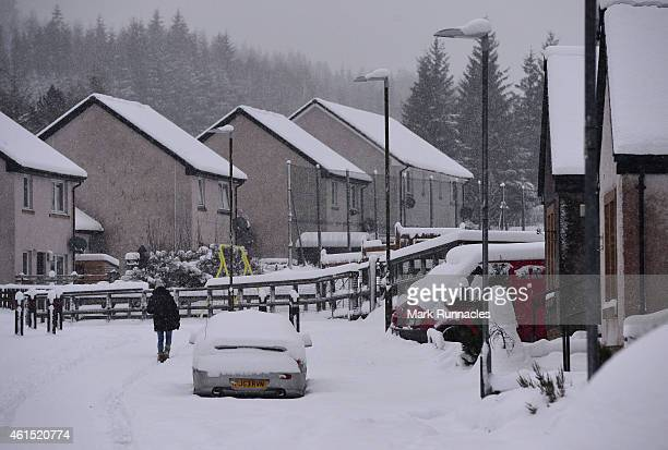 A woman walk along car tyre tracks in the snow as 46 inches of snow fell overnight in Tyndrum Stirlingshire The Met Office has issued amber 'be...