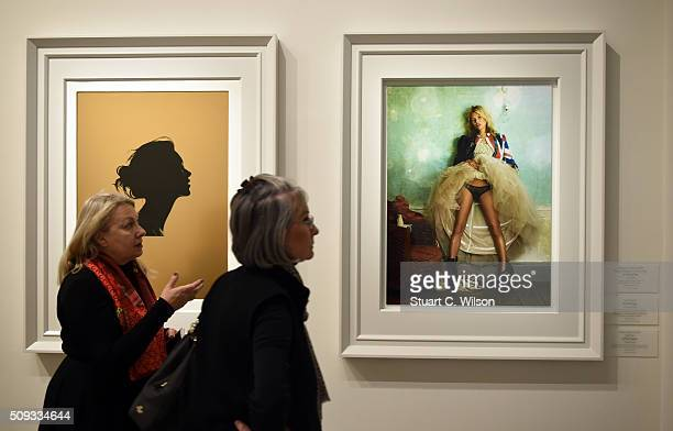 Woman walk by framed photos at the press preview for 'Vogue 100 A Century of Style' exhibiting the photographs that has been commissioned by British...