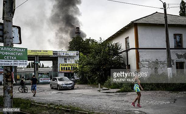 A woman walk in a street as smoke rises from an old factory after shelling rocked the area on July 21 2014 in the rebel stronghold of Donetsk in...