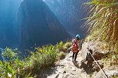 Woman walk in beautiful mountain landscape in summer bright vivid day light