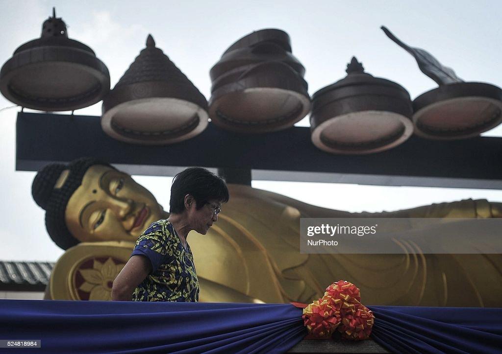 A woman walk past a statue of Buddha during Vesak Day celebrations at a Buddhist temple in Kuala Lumpur Malaysia on May 13 2014 Photo Mohd FIrdaus...