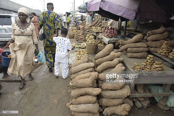 A woman walk past tubers of yam on display for sale at Mile 12 market in Lagos on June 21 2016 Ordinary Nigerians are feeling the full effects of...