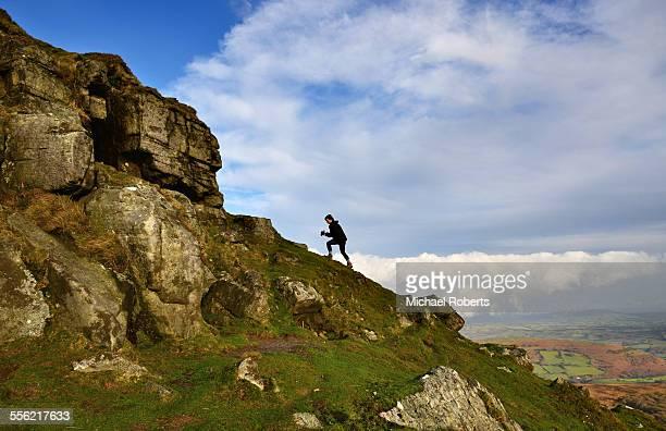 Woman walker climbing Sugar Loaf, Black Mountains