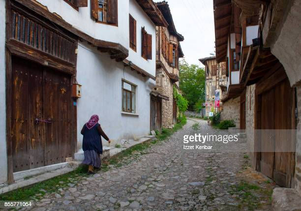 Woman walkimh alond old wooden mansions of Yoruk village near Safranbolu, Karabuk, Turkey