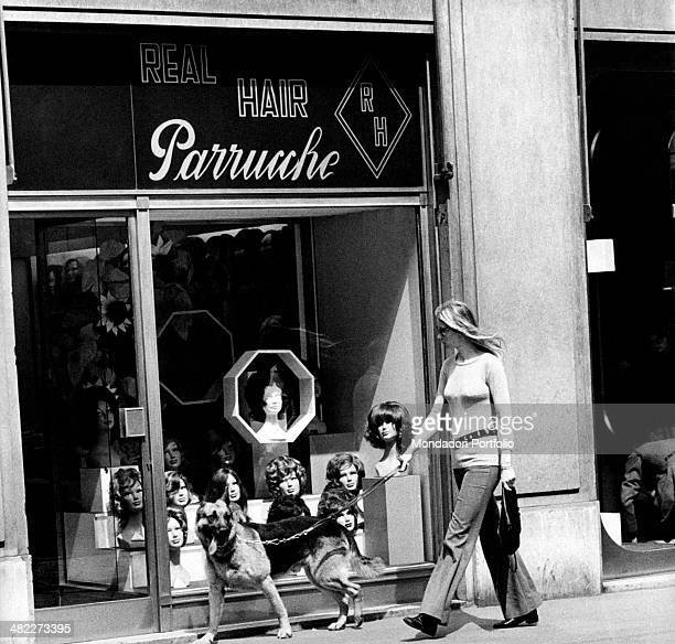 A woman walking a German Shepherd dog watching the window of a wig shop Milan 1971