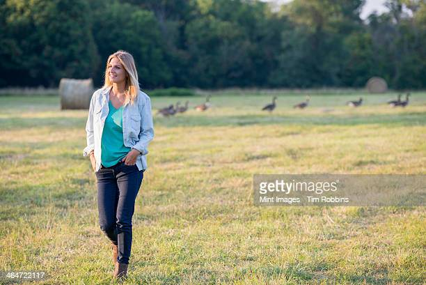 A woman walking across a field,away from a flock of geese outdoors in the fresh air.