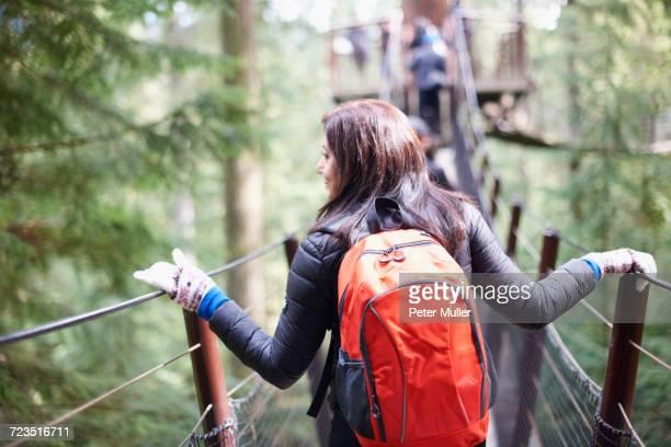 Woman walking across Capilano suspension bridge, rear view, Vancouver, Canada
