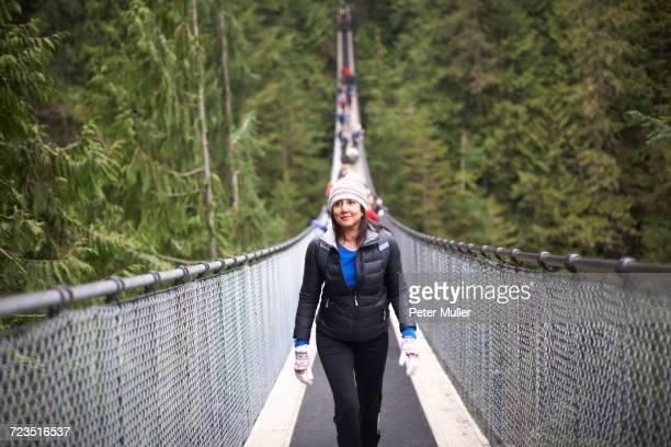 Woman walking across Capilano suspension bridge, Vancouver, Canada