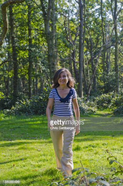 woman walking across clearing in forest