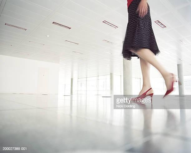 Woman walking across empty office, low section (Blurred Motion)