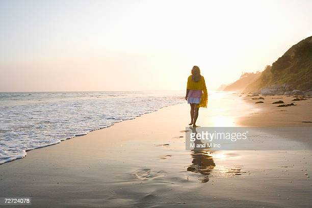 Woman walking across wet sand on beach, sunset