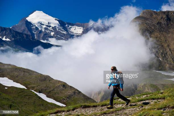 A woman walking alone at high altitude in the snowcapped mountains