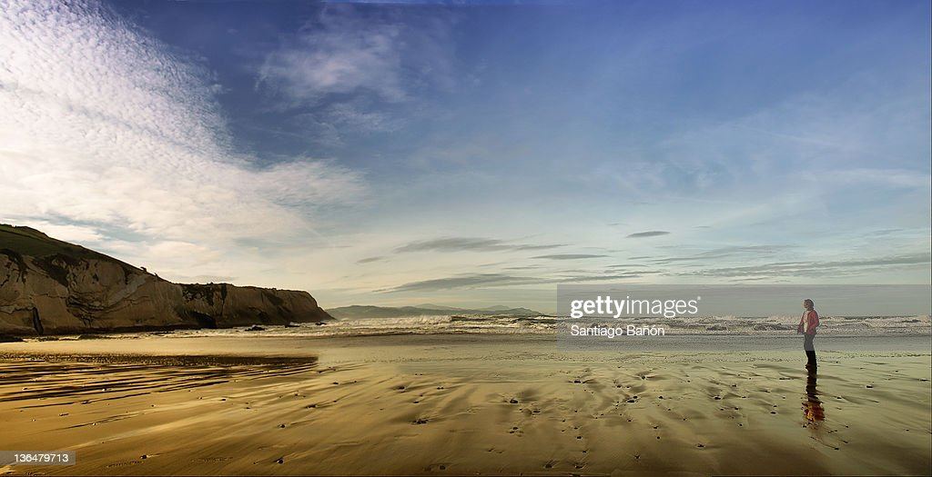Woman walking alone in beach : Stock Photo