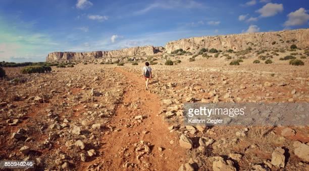 Woman walking alone on dirt road, Sicily