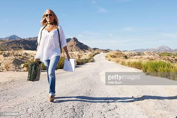 Woman walking alone on dusty road