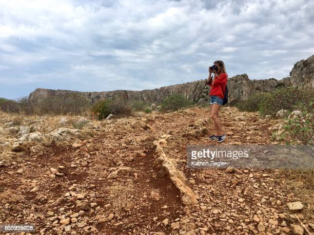 Woman walking alone on Sicilian dirt road, taking pictures of the scenery