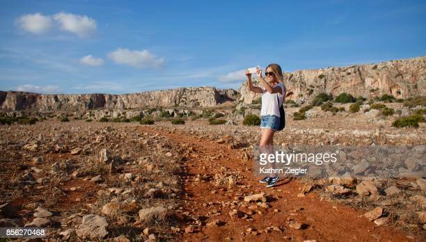 Woman walking alone on Sicilian dirt road, taking pictures of the scenery with smartphone