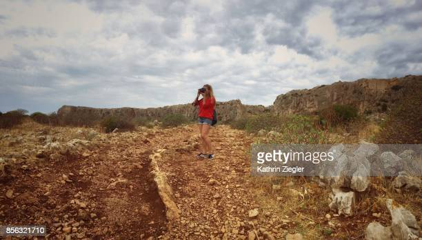 Woman walking alone on Sicilian dirt road, taking pictures of the scenery, panoramic image