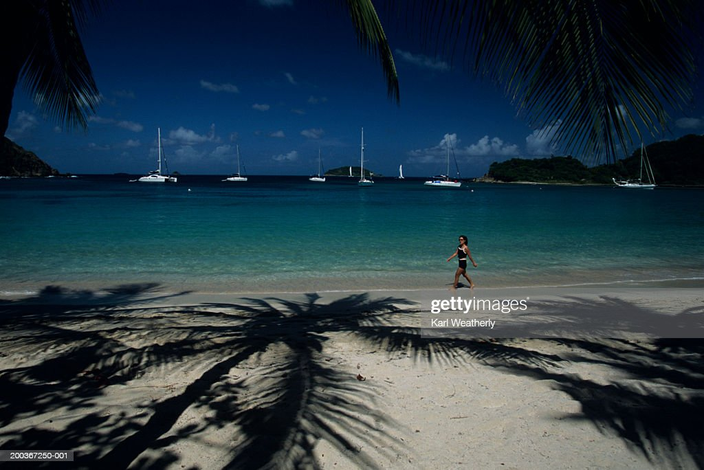 Woman walking along beach with palm trees, sailboats in background : Stock Photo