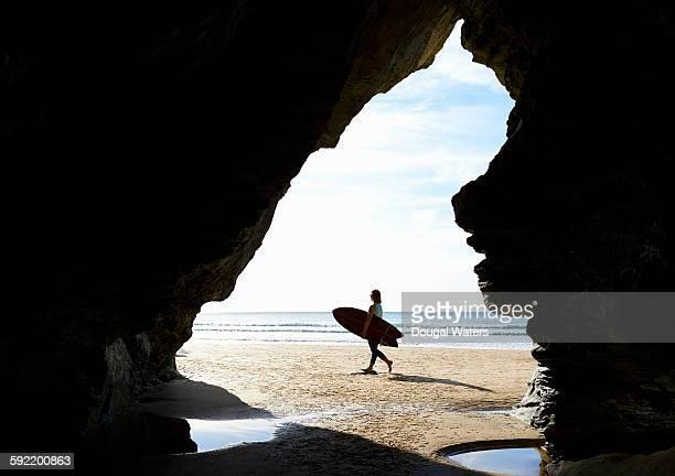 Woman walking along beach with surf board.