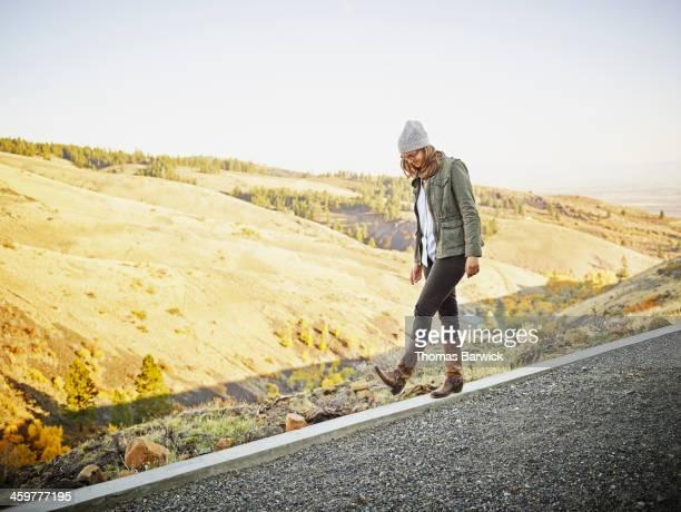 Woman walking along concrete wall on hillside