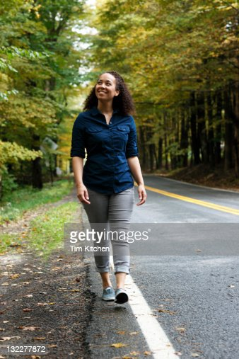 Woman walking along country road, smiling : Stock Photo