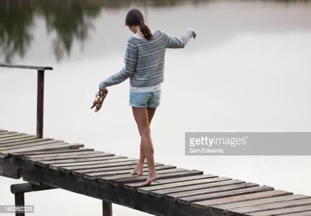 Woman walking along dock over lake