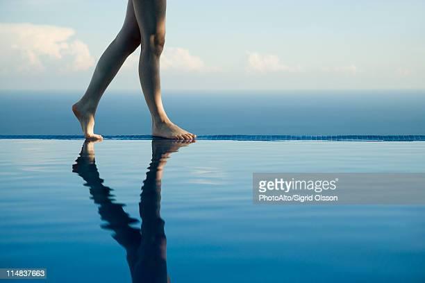 Woman walking along edge of infinity pool, low section