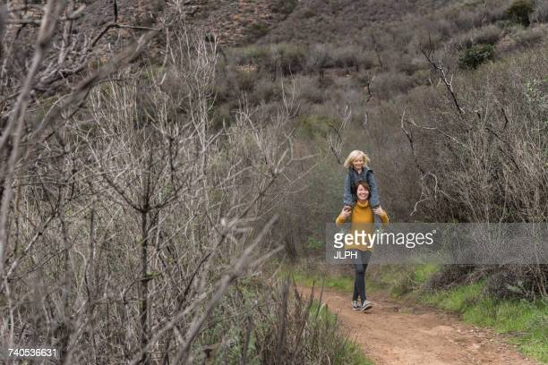 Woman walking along rural pathway, carrying son on shoulders
