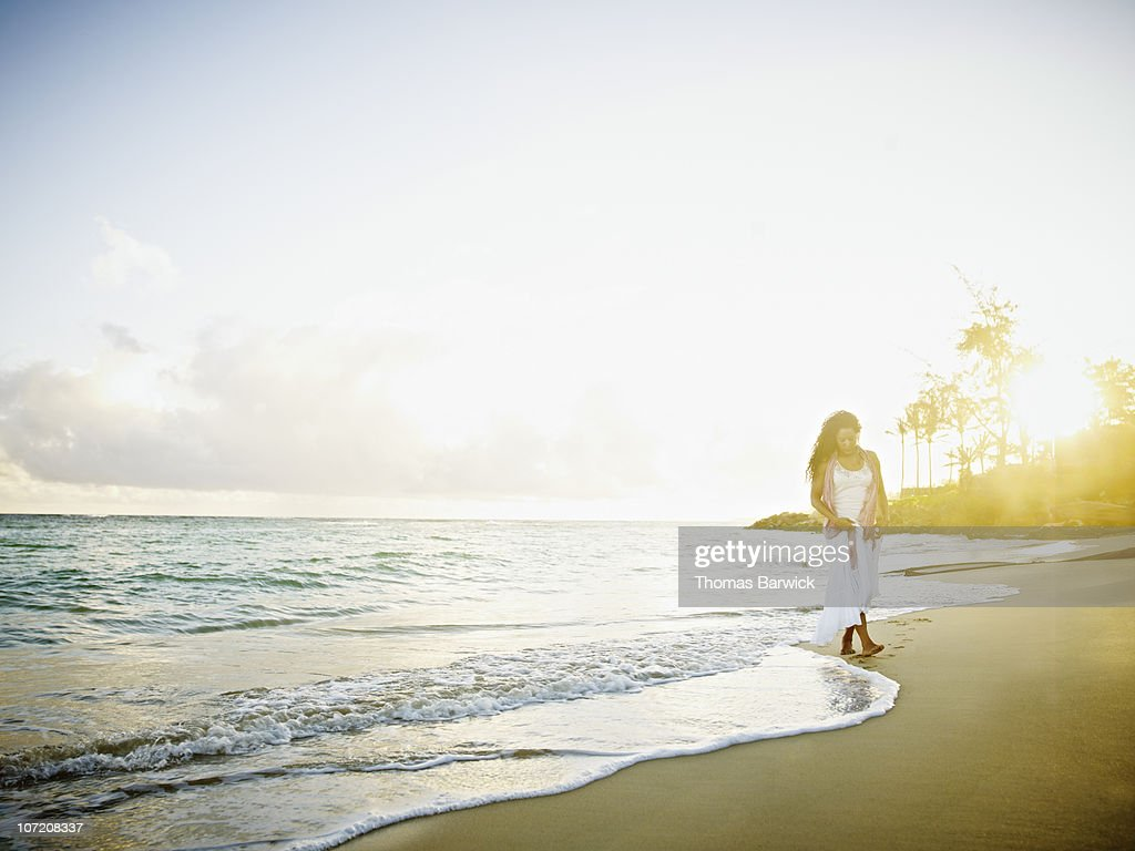 Woman walking along water on tropical beach : Stock Photo