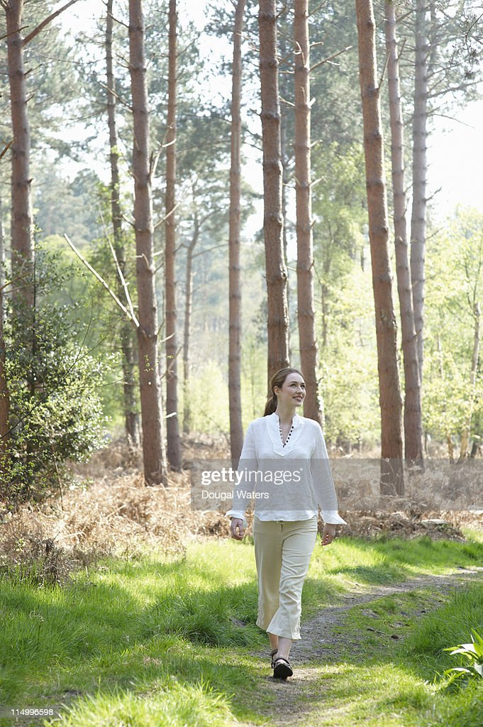 Woman walking along woodland path. : Stock Photo