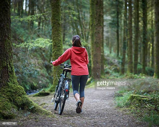 Woman walking along woodland path with bike.