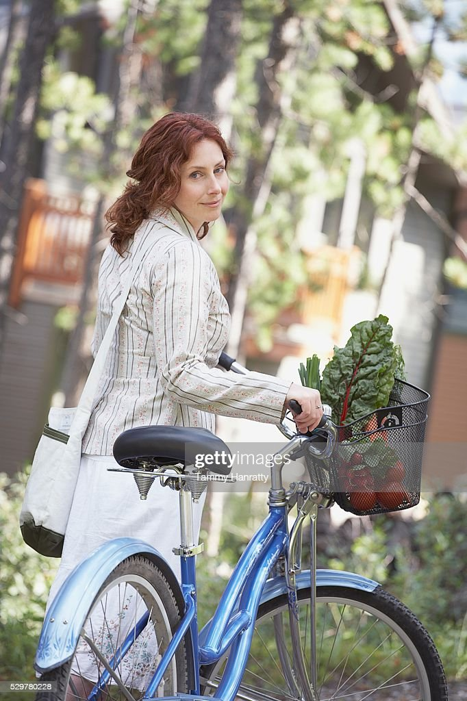 Woman walking alongside bicycle : Stock Photo
