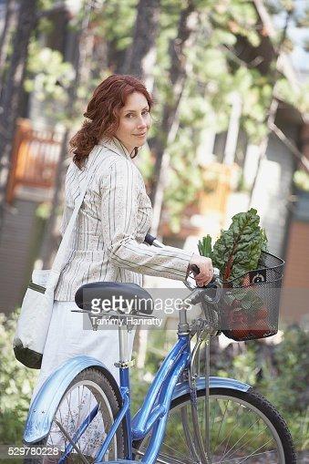 Woman walking alongside bicycle : Stock Photo