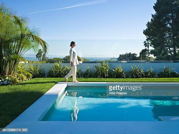 Woman walking around  swimming pool, side view