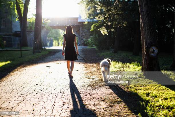 A woman walking at sunset with her dog