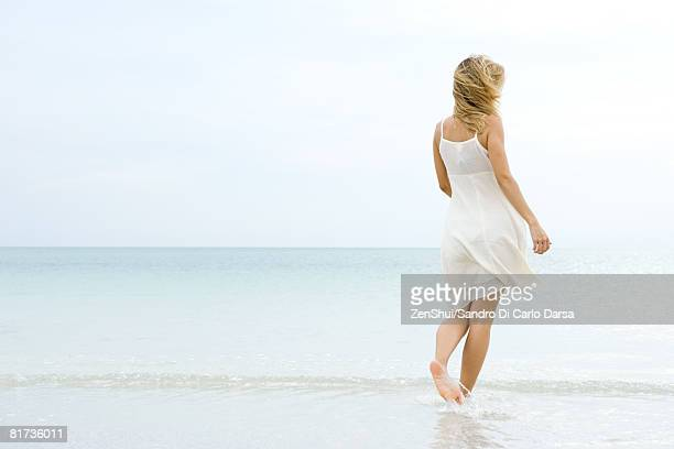 Woman walking at the beach, rear view