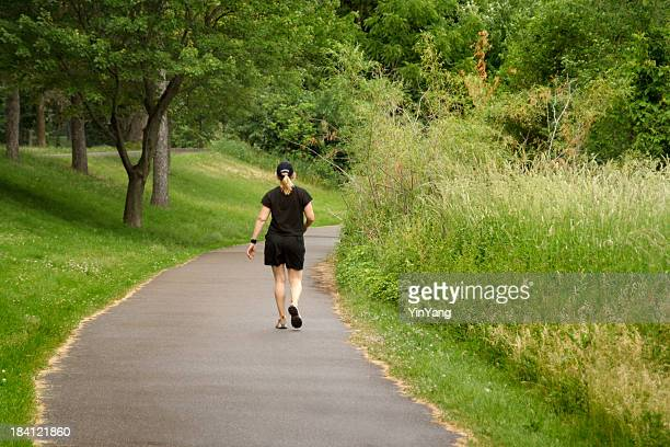 Mujer caminando lejos en camino, trotar o caminar en el parque