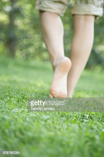 Woman walking bare foot in grass : Bildbanksbilder