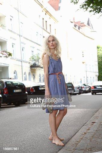 Woman walking barefoot on city street