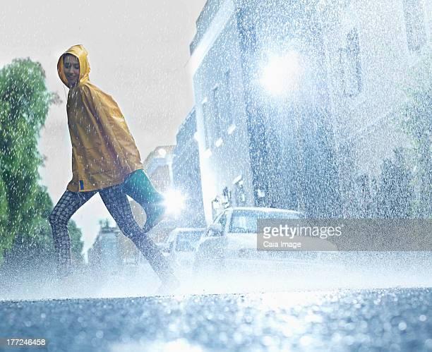 Woman walking barefoot on rainy street