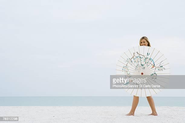 Woman walking behind parasol at the beach, smiling at camera