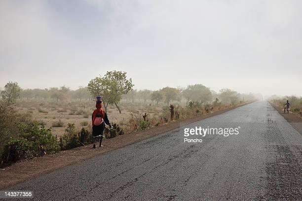 Woman walking beside a road