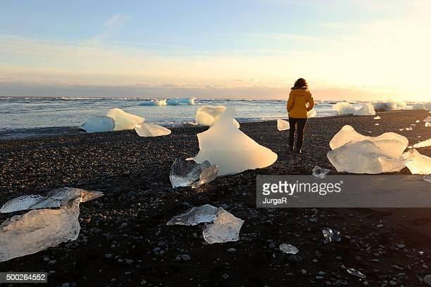 Frau, die zu Fuß zwischen den Eisbergen treiben am Lava Beach nahe Jokulsarlon Island