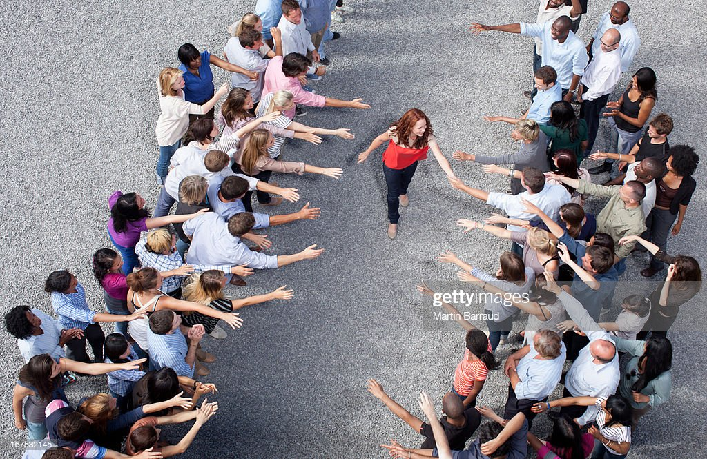 Woman walking between two groups of people, shaking hands : Stock Photo