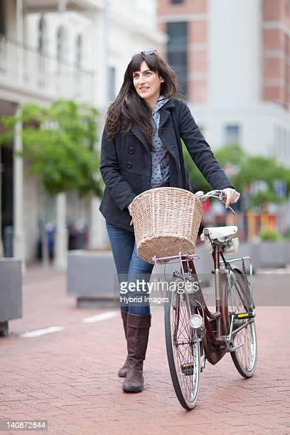 Woman walking bicycle on city street