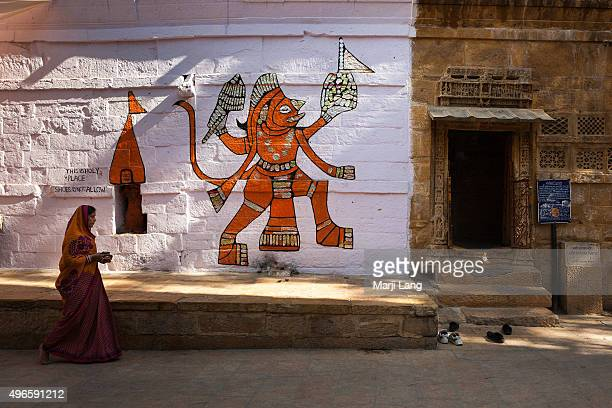 Woman walking by a Hindu temple with a Hanuman painting on the wall in Jaisalmer Rajasthan India