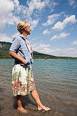 A mature woman walking along the shore of a mountain lake.